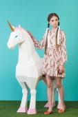 Fényképek divatos fiatal lány pózol a nagy fehér Egyszarvú a türkiz