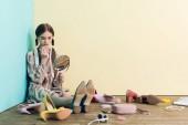 dospívající dívka použití make-up se zrcadlem a sedí na podlaze s nepořádkem