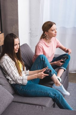 High angle view of two young female friends playing video game with joysticks in hands at home stock vector