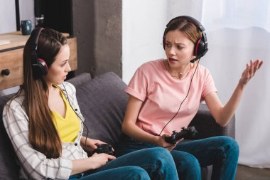 angry young woman in headphones with joystick in hand quarreling with female friend at home