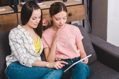 two young female friends with digital tablet sitting on sofa at home