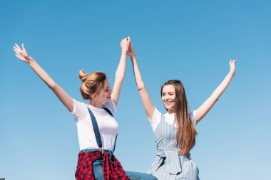 smiling young female friends holding hands against bright blue sky