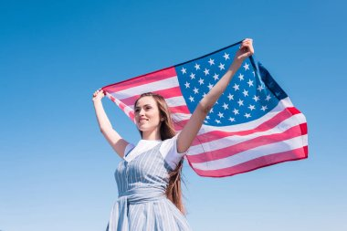 Young woman holding american flag against blue sky, independence day concept stock vector