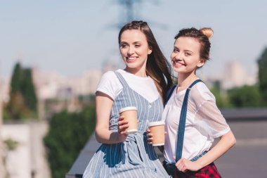 smiling young female friends with paper cups of coffee at rooftop