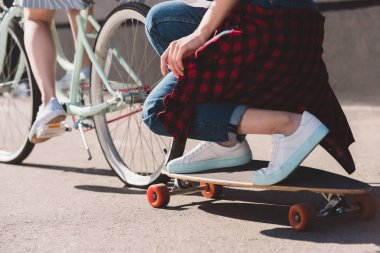 cropped shot of woman riding bicycle and towing her female friend on skateboard