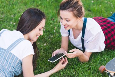 smiling female friends laying on grass with smartphone and skateboard in park