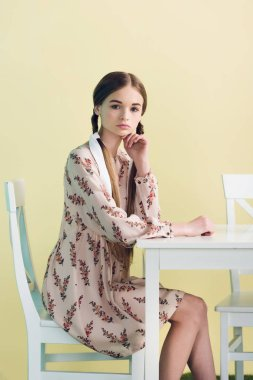 beautiful stylish teen girl with braids sitting at table, isolated on yellow