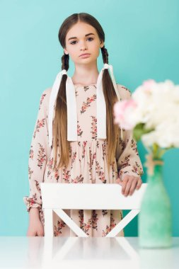 teen girl with braids posing near table with flowers, isolated on blue