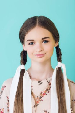 portrait of smiling elegant youth girl with braids, isolated on blue