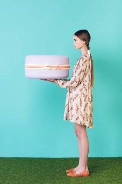 Fashionable teen girl holding big purple macaron, on turquoise stock vector