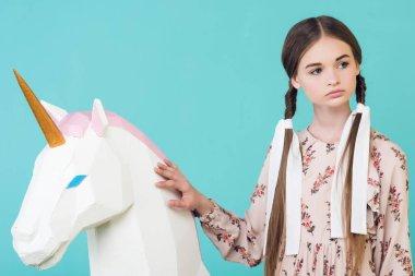 beautiful teen girl posing with big white unicorn, isolated on turquoise