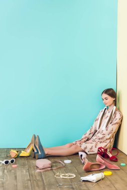 stylish female teenager sitting on floor with mess