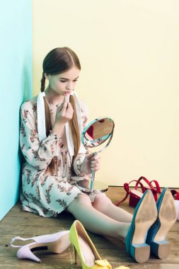attractive youth girl applying lipstick with mirror while sitting on floor with mess