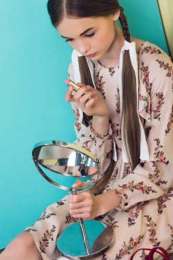 beautiful teen girl applying lipstick with mirror