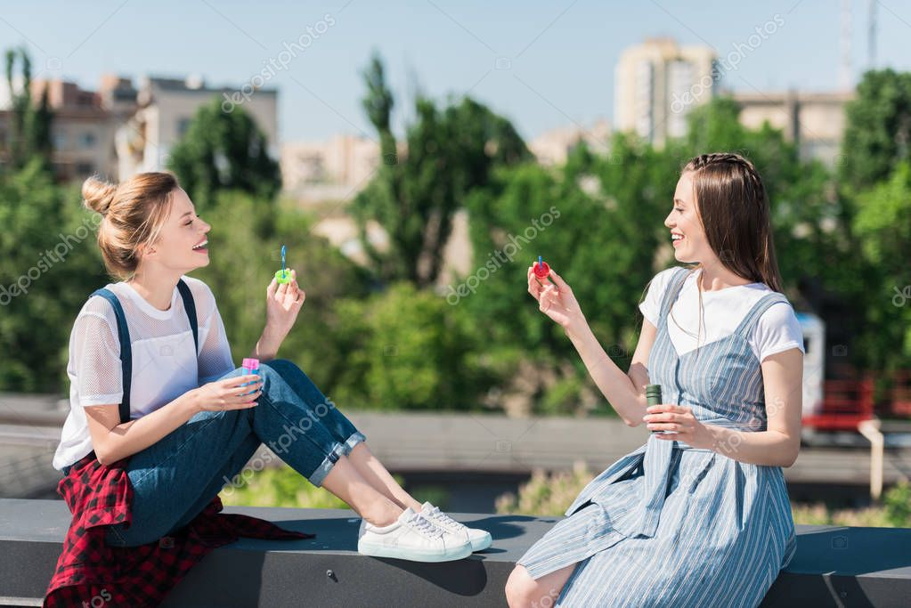 side view of two smiling female friends using bubble blowers at rooftop