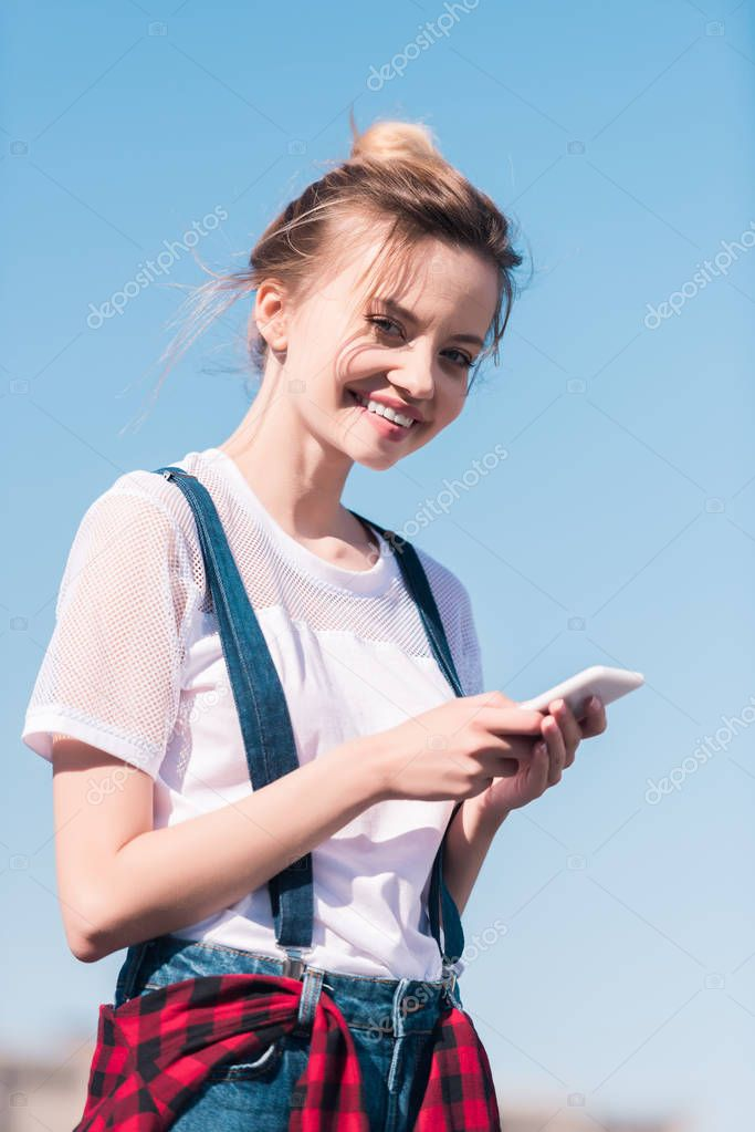 smiling young woman with smartphone against bright blue sky
