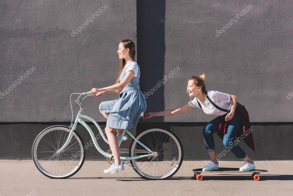 side view of woman riding bicycle and towing her smiling female friend on skateboard