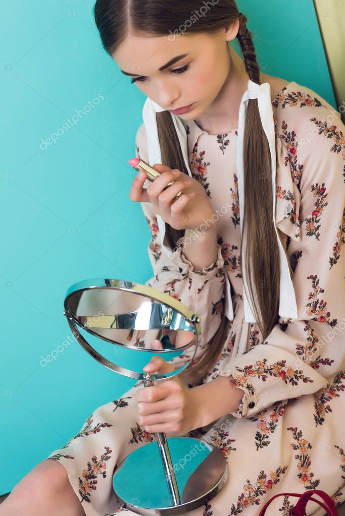 beautiful teen girl applying lipstick with mirror
