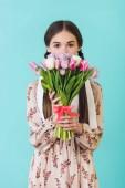 Fotografie atraktivní dívka v letních šatech drží kytici tulipánů, izolované na modré