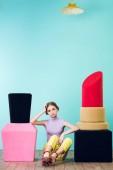 Elegantní módní dívka sedí mezi velkými nehty a rtěnku na podlaze