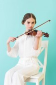 Fotografie teen girl playing violin and sitting on chair, isolated on turquoise