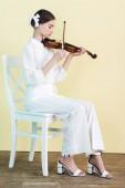 Fényképek tinédzser, fehér ruhában, hegedül, és ül a székre