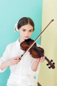 teen girl in trendy white outfit playing violin