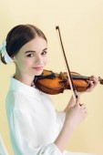 Fotografie attractive teen girl playing violin, isolated on yellow