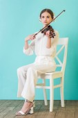 Fotografie attractive teen musician playing violin and sitting on chair, on blue