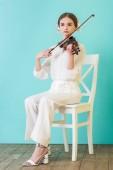Fényképek vonzó tini zenész hegedül, és ül a székre, a kék