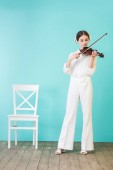 Fotografie beautiful teen girl playing violin, on blue