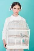 Fotografie Teen dívka v bílých hospodářství klec s papoušek, izolované na tyrkysové