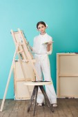 attractive teen artist painting on easel with brush and palette in workshop