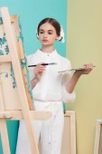 beautiful teen artist painting on easel with brush and palette