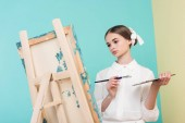 beautiful teen artist painting on easel with brush and palette, on turquoise