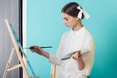 Fotografia pittura su cavalletto con pennello e la tavolozza, il turchese dellartista alla moda giovanile