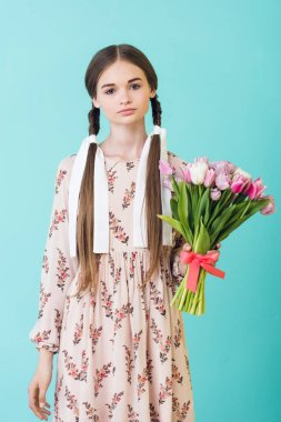 stylish teen girl with braids in summer dress holding bouquet of tulips, isolated on blue