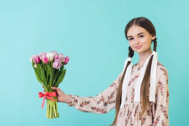 stylish girl with braids in summer dress holding tulips, isolated on turquoise