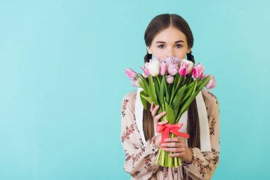 teen girl in trendy summer dress holding tulips, isolated on blue