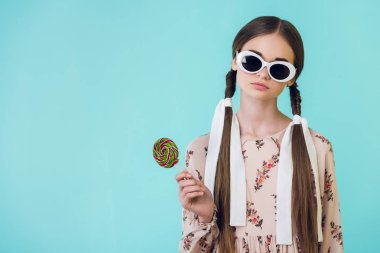 fashionable teen girl in sunglasses with braids holding lollipop, isolated on blue