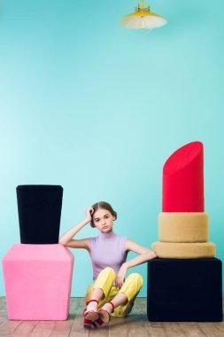 elegant fashionable girl sitting between big nail polish and lipstick on floor