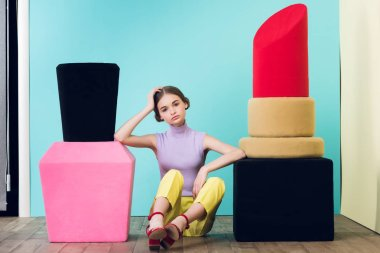 attractive teen girl sitting between big nail polish and lipstick