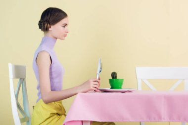 side view of girl eating cactus with fork and knife, diet concept