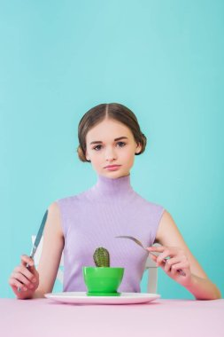 stylish female teenager eating cactus with fork and knife, diet concept