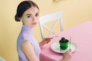 attractive teen girl eating cactus with fork and knife, diet concept