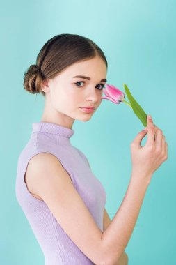 beautiful teen girl posing with pink tulip flower, isolated on turquoise