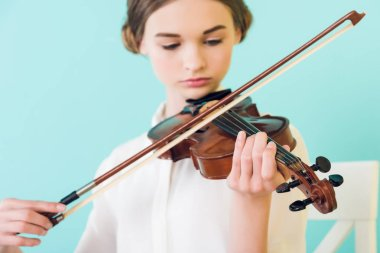 beautiful girl playing violin, isolated on blue