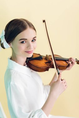 attractive teen girl playing violin, isolated on yellow