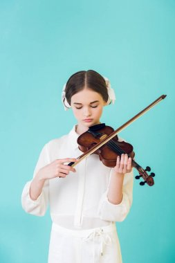 attractive teen girl playing violin, isolated on turquoise