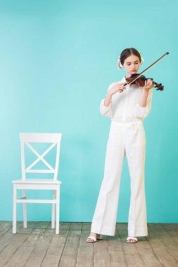beautiful teen girl playing violin, on blue